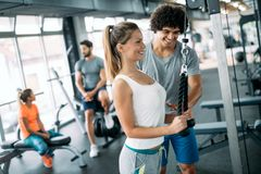 Personal trainer helping young woman reach goals royalty free stock photos
