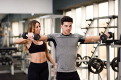 Personal trainer helping a young man lift weights. Female personal trainer helping a young men lift dumbells while working out in a gym Royalty Free Stock Images