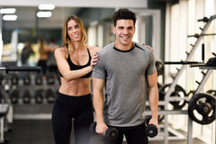 Personal trainer helping a young man lift weights. Female personal trainer helping a young men lift dumbells while working out in a gym Royalty Free Stock Photography