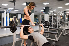 Personal trainer helping a young man lift weights. Female personal trainer helping a young men lift weights while working out in a gym Royalty Free Stock Photography