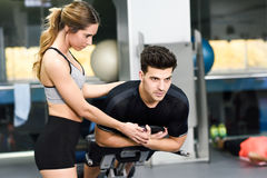 Personal trainer helping a young man lift weights. Female personal trainer helping a young men lift weights while working out in a gym Stock Photography