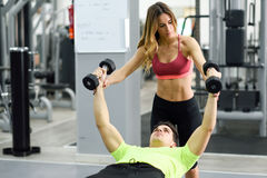 Personal trainer helping a young man lift weights. Female personal trainer helping a young men lift weights while working out in a gym Royalty Free Stock Photos