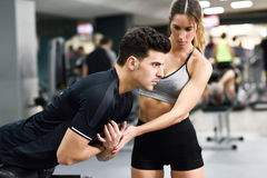 Personal trainer helping a young man lift weights. Female personal trainer helping a young men lift weights while working out in a gym Royalty Free Stock Images