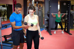 Personal trainer helping young woman Royalty Free Stock Photo