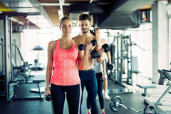 Personal trainer helping young woman with exercises for biceps Royalty Free Stock Photos