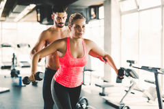Personal trainer helping young woman with exercises for shoulders Royalty Free Stock Photos