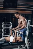 Personal trainer helping a young woman lift a barbell while working out in a gym. Personal trainer helping a young women lift a barbell while working out in a Royalty Free Stock Photography