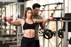 Personal trainer helping a young woman lift weights. Personal trainer helping a young women lift dumbells while working out in a gym Royalty Free Stock Images