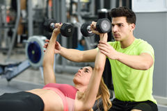 Personal trainer helping a young woman lift weights. Personal trainer helping a young women lift weights while working out in a gym Stock Photography