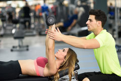 Personal trainer helping a young woman lift weights. Personal trainer helping a young women lift weights while working out in a gym Royalty Free Stock Photography