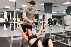 Personal trainer helping a young woman lift weights Stock Photo