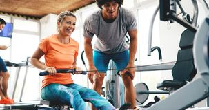 Personal trainer helping. Personal young trainer helping women in gym Stock Image