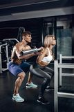 Personal trainer helping a young woman lift a barbell while working out in a gym. Personal trainer helping a young women lift a barbell while working out in a Royalty Free Stock Images
