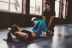 Personal trainer helps a girl with the gym exercises Royalty Free Stock Image