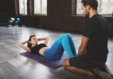 Personal trainer helps a girl with the gym exercises Stock Photos