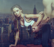 Personal trainer helps to woman in workout behind glass Stock Image