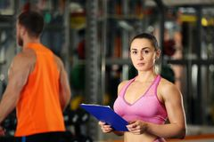 Personal trainer holding clipboard with training plan. In gym Stock Photo