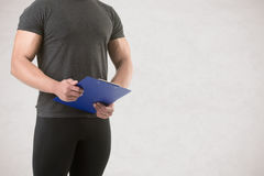 Personal Trainer Holding a Pad Royalty Free Stock Image