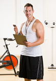 Personal trainer holding stop watch and clipboard Royalty Free Stock Photos