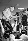 Personal trainer instructing a man with barbell Royalty Free Stock Image