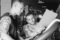 Personal trainer instructing sportsman Stock Photos