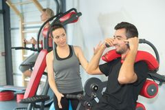 Personal trainer instructing trainee in gym Royalty Free Stock Image