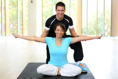 Personal trainer instructing woman in gymnastics Stock Photo