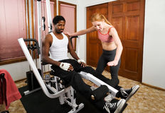Personal Trainer Instruction. A female personal trainer gives instruction on proper leg lifts Royalty Free Stock Photography
