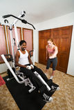 Personal Trainer Instruction. Female personal trainer tells her client how to lift his legs Royalty Free Stock Images
