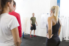 Personal trainer instructs fitness workout team. Instructor going through today's training plan at the fitness gym Stock Photos