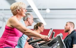 Personal trainer instructs senior woman about spinning at the gy Stock Images