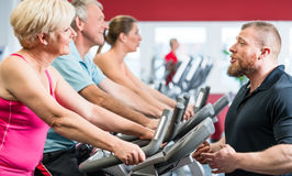 Personal trainer instructs senior woman about spinning at the gy Royalty Free Stock Photos