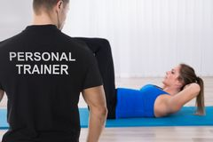 Personal Trainer Looking At Woman Doing Exercise. Personal Trainer Looking At Young Woman Doing Exercise On Yoga Mat royalty free stock photography