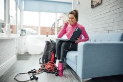 Personal Trainer Making Bookings at Home. Self-employed personal trainer is making bookings over the phone at home Stock Images