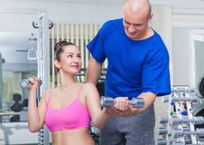 Personal trainer. Man personal trainer assisting a women lifting weights Stock Image