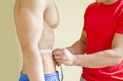 Personal trainer measuring client's waist with tape meter. Personal trainer measuring shirtless muscular client's waist with tape meter Stock Photography