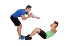 Personal trainer with a megaphone and boy making abdominal Stock Images