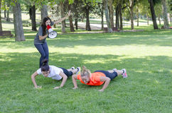 Personal trainer with a megaphone and two women doing exercises. Royalty Free Stock Photography
