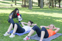 Personal trainer with a megaphone and two women making abdominal. Stock Images