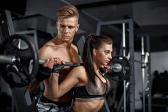 Personal trainer model helps woman model to lift the barbell in the gym stock photo