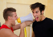 Personal trainer motivating client yelling with megaphone. Personal trainer motivating male client by yelling against him with megaphone Stock Image