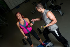 Personal trainer motivating woman in gym Stock Image