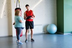 Personal Trainer Presenting training Plan. Full length portrait of handsome fitness instructor talking to obese women during personal training in gym, copy space Royalty Free Stock Image