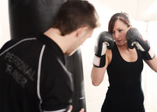 Personal trainer on punch bag. Woman working out with personal trainer on punch bag in gym Royalty Free Stock Image