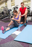 Personal trainer rubbing clients shoulders on mat Stock Photography
