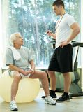 Personal trainer with senior man. Personal trainer explains to a senior men how to do exercise on a fitness ball Royalty Free Stock Photos