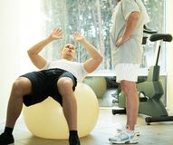 Personal trainer and senior man in fitness club Royalty Free Stock Images