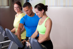 Personal trainer setting treadmill Royalty Free Stock Photos
