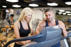 Personal trainer show treadmill for blonde woman in gym Royalty Free Stock Photo