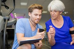 Personal trainer showing results to senior woman stock photos